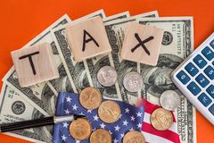 Hölzerne Würfelsteuer mit Flagge, Dollar, Münze und Taschenrechner Lizenzfreies Stockfoto