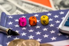 Hölzerne Würfelsteuer mit Flagge, Dollar, Münze und Taschenrechner auf Orange Lizenzfreies Stockfoto