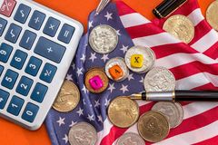 Hölzerne Würfelsteuer mit Flagge, Dollar, Münze und Taschenrechner auf Orange Lizenzfreie Stockfotos