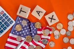 Hölzerne Würfelsteuer mit Flagge, Dollar, Münze und Taschenrechner auf Orange Stockfoto