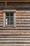 Hölzerne Wand des alten Blockhauses mit dem Fenster halb geschlossen mit Vorhang Lizenzfreies Stockbild