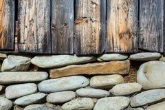 Hölzerne Wand und Stein-Keller des traditionellen ländlichen Bungalows Stockfotografie