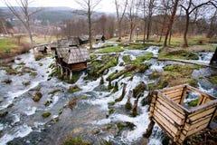 Hölzerne Wassermühlen steht auf einem schnell fließenden Fluss Lizenzfreie Stockfotografie