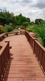 Hölzerne Wegweise mit Landschaft des Gartens Stockfoto