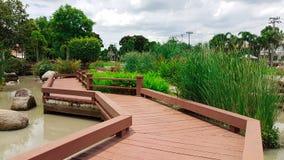 Hölzerne Wegweise mit Landschaft des Gartens und des Teichs Lizenzfreies Stockbild
