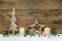 Hölzerne Weihnachtsdekoration mit grünen Bällen, Kerzen und Sternen an Lizenzfreies Stockfoto