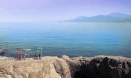 Hölzerne Weinlesetabelle stellte mit Hintergrund des blauen Himmels und des Meeres ein Lizenzfreies Stockfoto