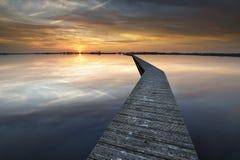 Hölzerne Weise auf Wasser bei Sonnenuntergang stockfoto