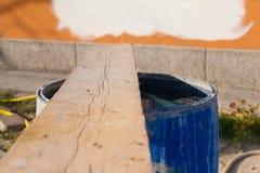 Hölzerne Welle über blauem wassergefülltem Plastikfaß in der Baustelle in Italien mit farbigen Kunststoffrohren auf dem Hintergru Stockbild