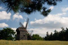 Hölzerne Windmühle, die mitten in Feldern steht Stockfoto