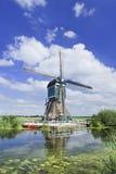 Hölzerne Windmühle nahe einem Kanal an einem Sommertag mit blauem Himmel und Wolken, die Niederlande Stockfotos