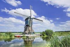 Hölzerne Windmühle nahe einem Kanal an einem Sommertag mit blauem Himmel und Wolken, die Niederlande Stockfotografie