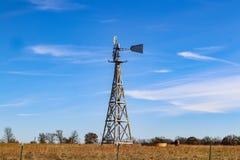 Hölzerne Windmühle pumpt Wasser in starkes für Kühe heraus in der Winterweide unter blauen Himmel mit wispy Wolken und hinter rus lizenzfreies stockbild