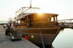 Hölzerne Yacht wird am Meer, am Abend oder am frühen Morgen, Sonne festgemacht lizenzfreies stockfoto