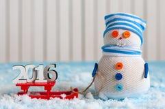 Hölzerne Zahlen des guten Rutsch ins Neue Jahr 2016 auf rotem Schlitten und Stockfotografie