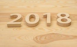 Hölzerne Zahlen, die 2018, geschnitzt vom hellen Holz auf dem backg bilden Lizenzfreie Stockbilder