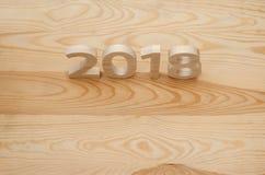 Hölzerne Zahlen, die 2018, geschnitzt vom hellen Holz auf dem backg bilden Lizenzfreies Stockfoto