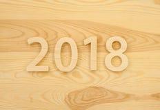 Hölzerne Zahlen, die 2018, geschnitzt vom hellen Holz auf dem backg bilden Stockfoto