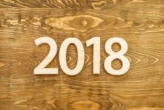 Hölzerne Zahlen, die 2018, geschnitzt vom hellen Holz auf dem backg bilden Stockbilder