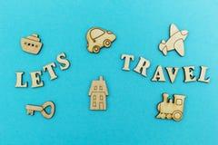 Hölzerne Zahlen eines Flugzeuges, ein Zug, ein Schiff, ein Auto Die Aufschrift 'ließ uns auf einen blauen Hintergrund reisen ' lizenzfreie stockfotos