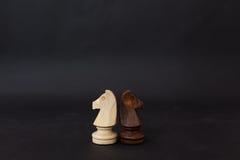 Hölzerne Zahlen eines Schwarzweiss-Pferds Schachfiguren auf einem schwarzen Hintergrund Stockfotos
