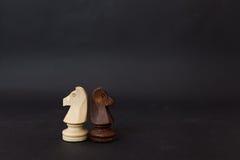Hölzerne Zahlen eines Schwarzweiss-Pferds Schachfiguren auf einem schwarzen Hintergrund Stockfoto