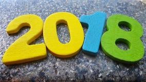 Hölzerne Zahlen, welche die Nr. 2018, für das neue Jahr 2018 auf einem abstrakten Hintergrund bilden Lizenzfreies Stockfoto