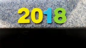 Hölzerne Zahlen, welche die Nr. 2018, für das neue Jahr 2018 auf einem abstrakten Hintergrund bilden Stockfotografie