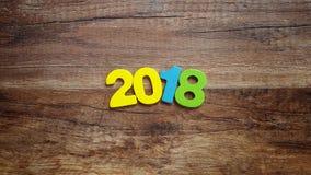 Hölzerne Zahlen, welche die Nr. 2018, für das neue Jahr 2018 auf einem hölzernen Hintergrund bilden Stockfotografie