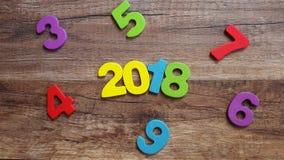 Hölzerne Zahlen, welche die Nr. 2018, für das neue Jahr 2018 auf einem hölzernen Hintergrund bilden Stockfotos