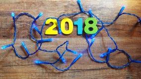 Hölzerne Zahlen, welche die Nr. 2018, für das neue Jahr 2018 auf einem hölzernen Hintergrund bilden Lizenzfreies Stockfoto
