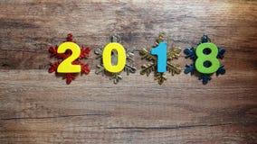 Hölzerne Zahlen, welche die Nr. 2018, für das neue Jahr 2018 auf einem hölzernen Hintergrund bilden Stockfoto