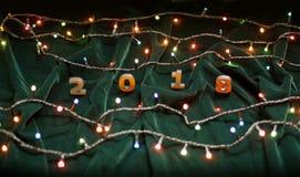 Hölzerne Zahlen, welche die Nr. 2018 und die Weihnachtslichter auf a bilden Stockbild