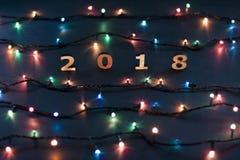 Hölzerne Zahlen, welche die Nr. 2018 und die Weihnachtslichter auf a bilden Stockbilder