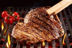 Hölzerne Zangen, die Rindfleisch auf Grill aufheben Stockfoto