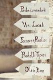 Hölzerne Zeichenpfeilspitze mit typischen Produkten Italiens südlichen Puglia-Italieners Stockfotografie