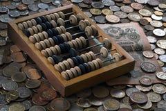 Hölzerner Abakus, Banknoten und eine Vielzahl von Münzen Stockfoto