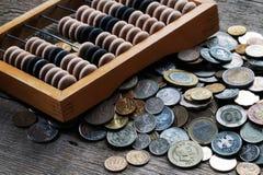 Hölzerner Abakus und ein Bündel verschiedene Münzen Stockbild