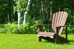 Hölzerner Adirondack-Sommergartenstuhl draußen auf dem grünen Gras Stockbild