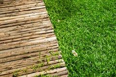 Hölzerner Bürgersteig und grüner Rasen für Hintergrund oder Beschaffenheit stockfoto