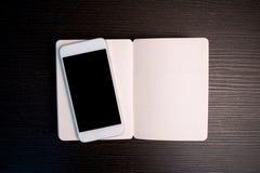 Hölzerner Bürotisch mit intelligentem Telefon und Sketchbook Stockfoto