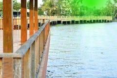 Hölzerner Balkon oder hölzerne Terrasse nahe dem Fluss mit Sonnenlicht Lizenzfreie Stockfotos