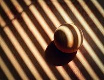 Hölzerner Ball bedeckt mit dem Schatten von Rollos Lizenzfreies Stockfoto