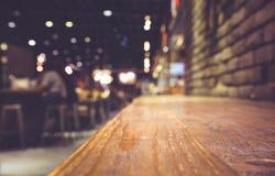 Hölzerner Bartisch auf Café in der dunklen Nacht mit Leuten stockfotografie