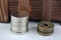 Hölzerner Behälter mit den neuen und gealterten Münzen Stockfoto