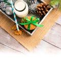 Hölzerner Behälter mit Milch, Plätzchen und Weihnachtsflitter Stockbild