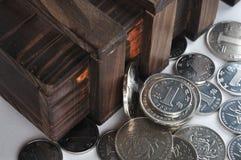 Hölzerner Behälter und Münzen Stockfotos