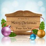 Hölzerner Beschaffenheitsrahmen für Weihnachten mit bunten Bällen, Stechpalmenblatt und Schneefällen Stockfoto