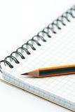 Hölzerner Bleistift auf dem Schulnotizbuch über weißem Hintergrund Stockbilder