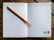 Hölzerner Bleistift auf Notizbuch Lizenzfreies Stockbild